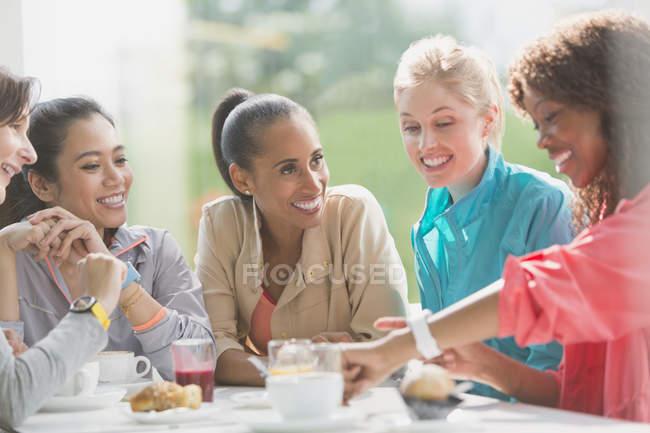 Les femmes parlent et regardent la montre intelligente à la table de café après l'entraînement — Photo de stock