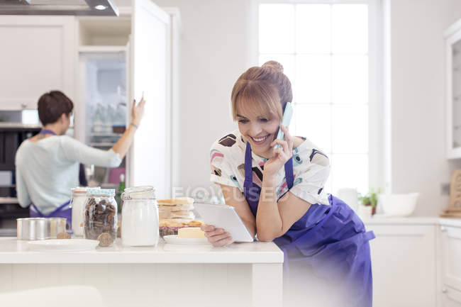Female caterers baking and working in kitchen, talking on cell phone and using digital tablet — Stock Photo