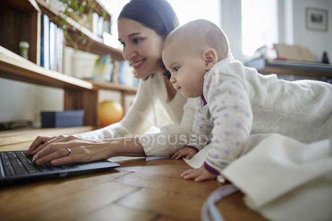 Bambino figlia guardando la madre a digitare sul computer portatile sul pavimento — Foto stock