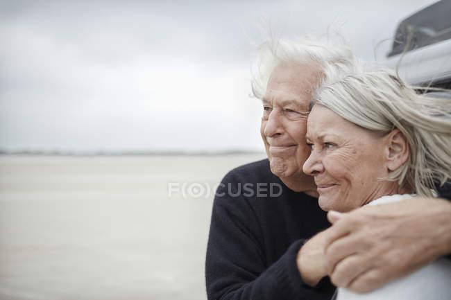 Affettuosa coppia anziana che abbraccia e distoglie lo sguardo sulla spiaggia — Foto stock