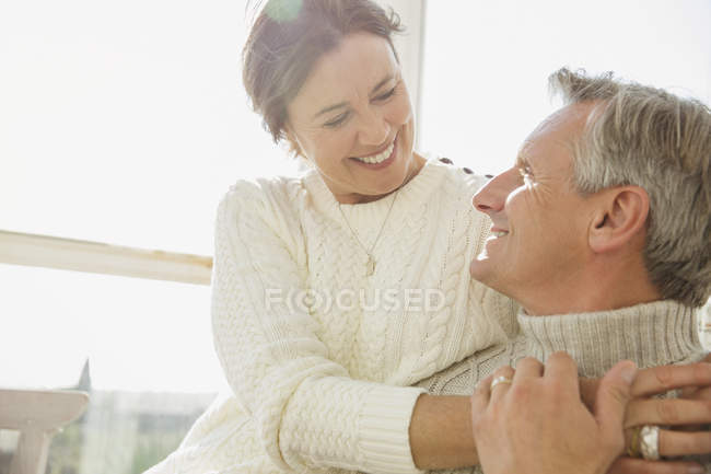 Affectionate mature couple hugging on sunny porch — Stock Photo