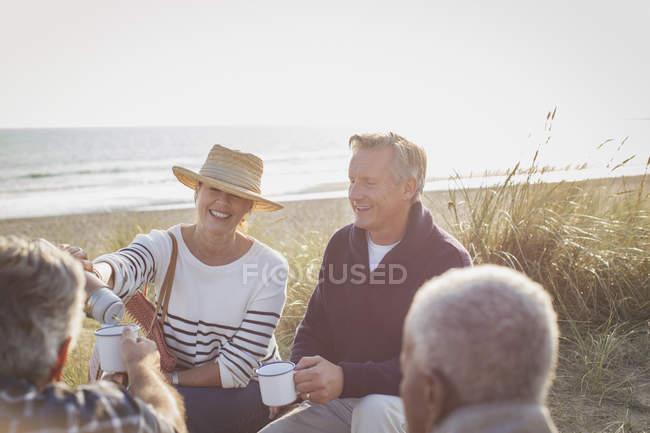 Senior couples drinking coffee on sunny beach — Stock Photo