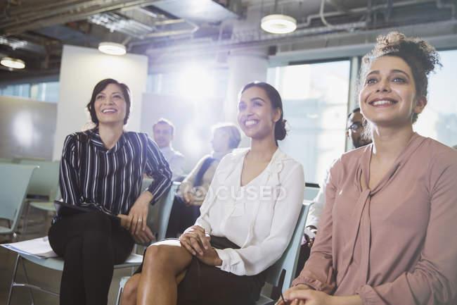 Femmes d'affaires souriantes à l'écoute en réunion au bureau — Photo de stock