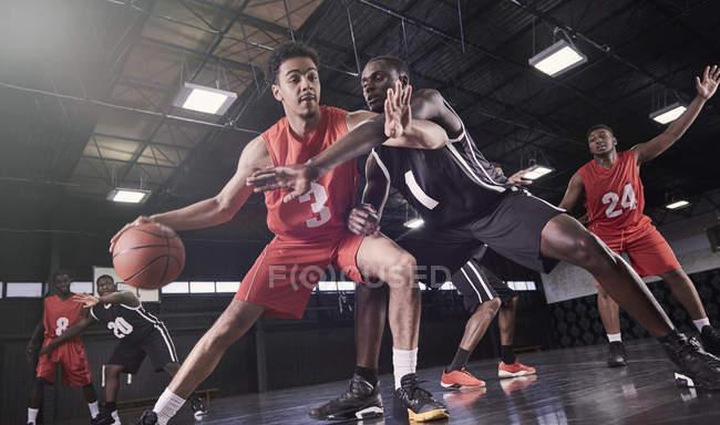 Молодые мужчины баскетболистов, играя на суде в гимназии — стоковое фото