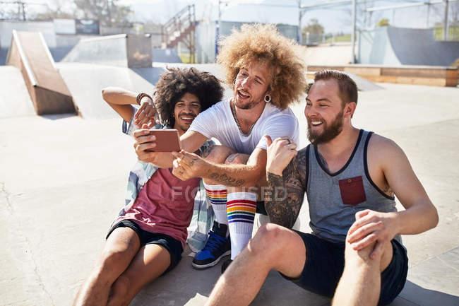 Amigos con la cámara del teléfono tomando selfie en Parque soleado - foto de stock