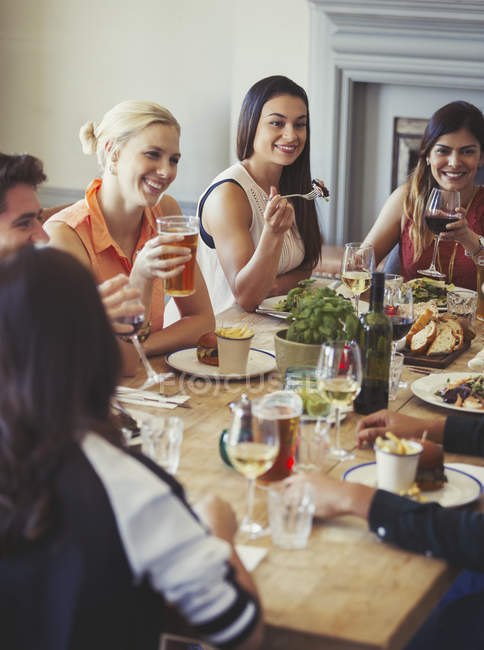 Friends talking and dining at restaurant table — Stock Photo