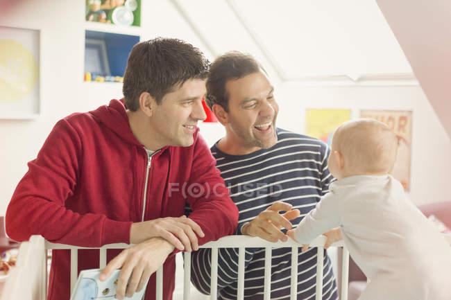 Maschio gay genitori guardando bambino figlio in culla — Foto stock