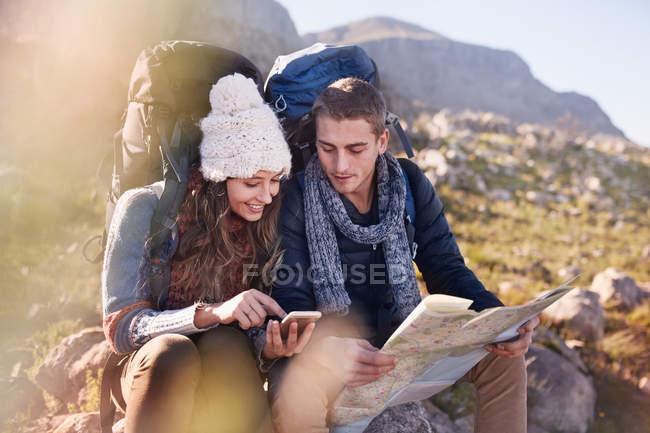 Coppia giovane con zaini escursionismo, riposo e controllo mappa e smartphone — Foto stock
