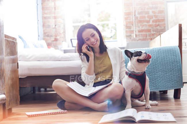 Mujer hablando por celular junto al Bulldog francés en el suelo - foto de stock