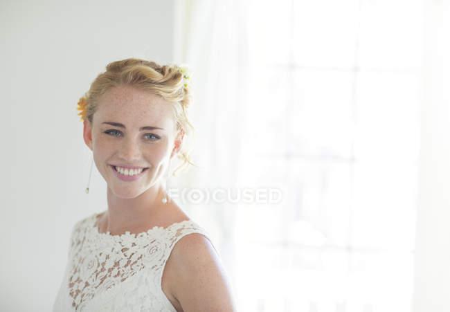 Retrato de novia sonriente en habitación soleada - foto de stock
