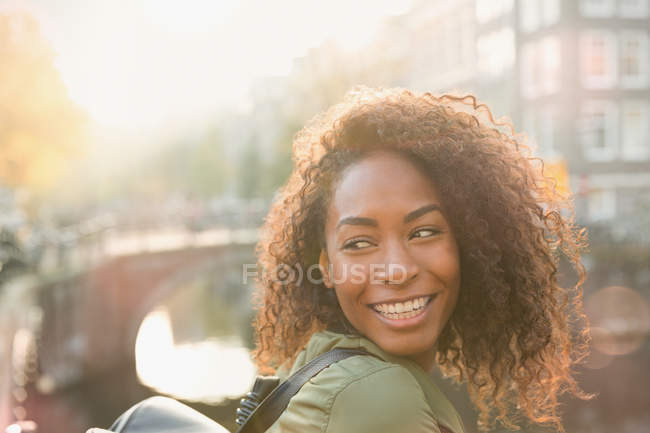 Smiling woman looking over shoulder — Stock Photo