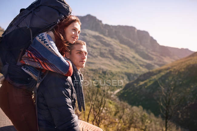 Affectionate young couple with backpack hiking, taking a break in sunny landscape — Stock Photo