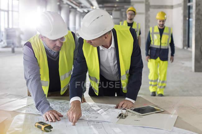 Engenheiros do sexo masculino discutindo plantas no canteiro de obras — Fotografia de Stock