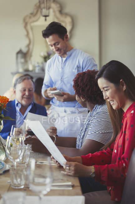 Mesero tomar la orden de amigos en mesa de restaurante con menú - foto de stock
