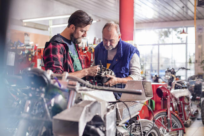 Male motorcycle mechanics repairing part in workshop — Stock Photo