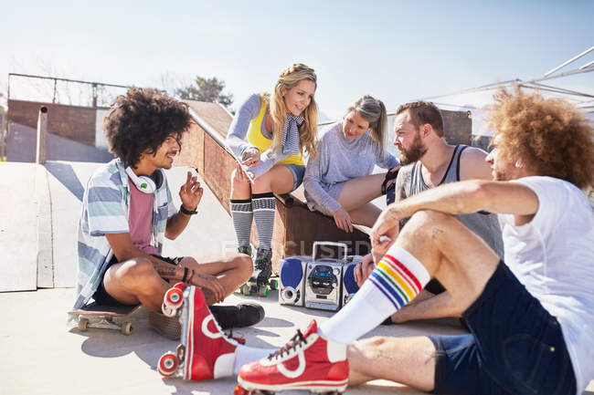 Friends in roller skates hanging out listening to music at sunny skate park — Stock Photo