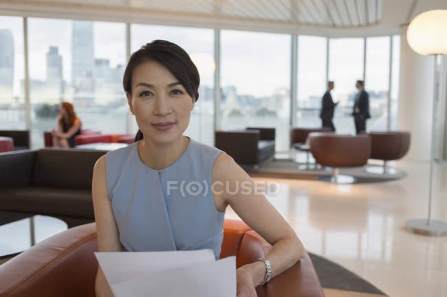 Portrait femme d'affaires confiante examinant la paperasserie dans le salon de bureau — Photo de stock