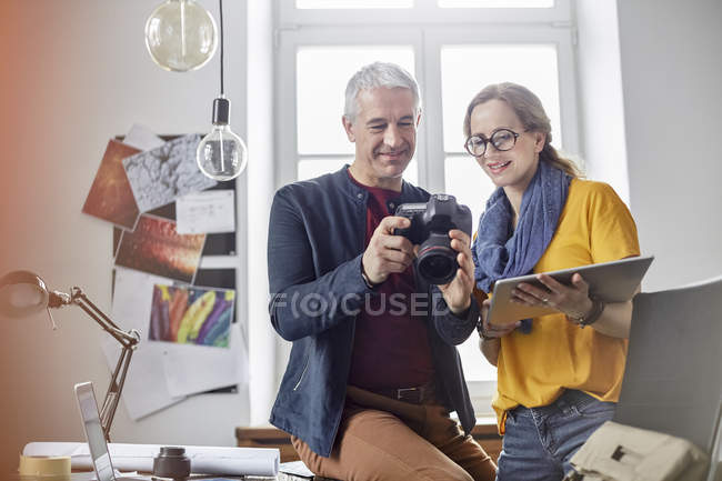 Photographers using digital tablet and digital camera in office — Stock Photo