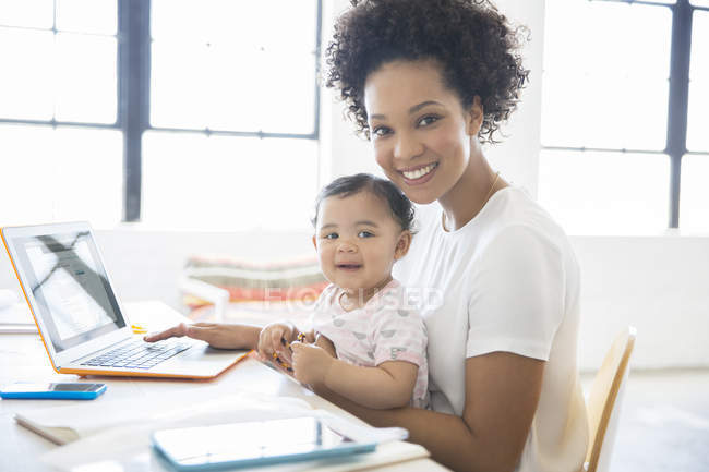 Mother working from home with daughter sitting on her lap — Stock Photo