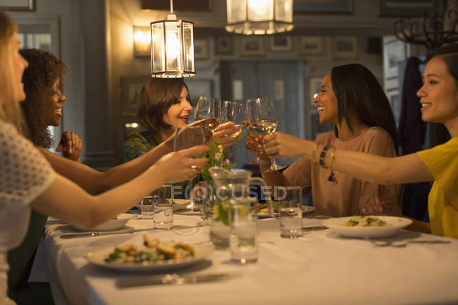 Women friends toasting white wine glasses at restaurant table — Stock Photo