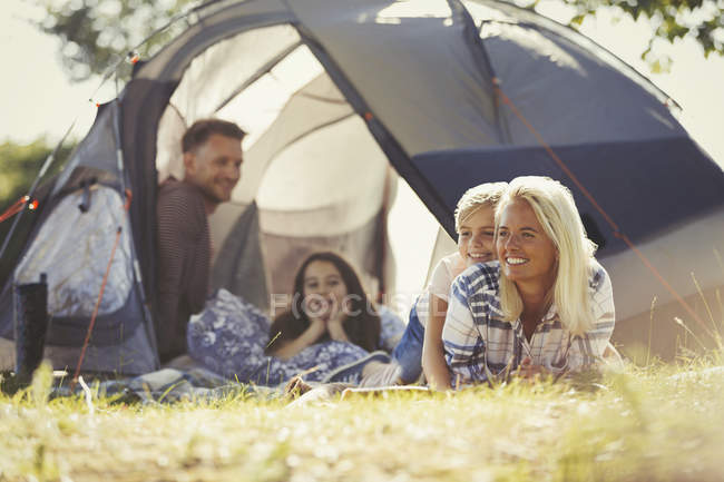 Smiling family relaxing outside sunny tent at campsite — Stock Photo