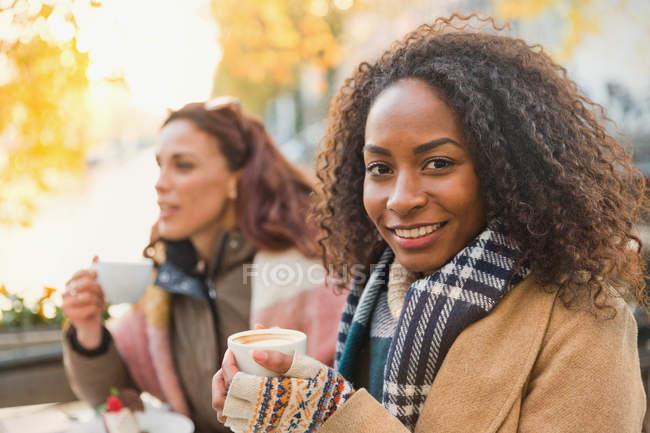 Retrato sorrindo jovem mulher em roupas quentes bebendo café expresso no café da calçada — Fotografia de Stock