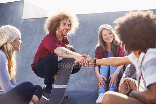 Friends with skateboards handshaking at sunny skate park — Stock Photo