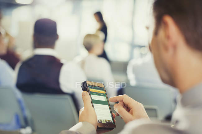 Businessman texting with cell phone in conference audience — Stock Photo