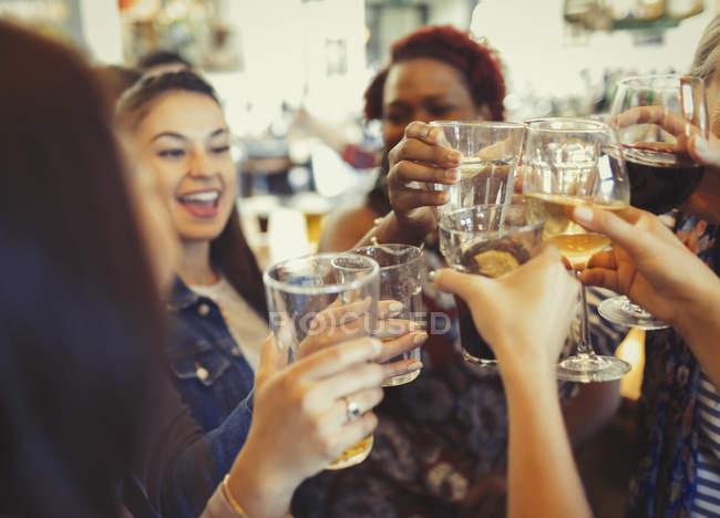 Mulheres entusiasmadas comemorando, brindando cerveja e copos de vinho no bar — Fotografia de Stock