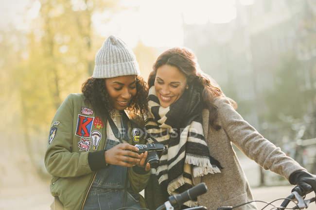 Junge Freundinnen mit Fahrrädern mit Digitalkamera auf der städtischen Herbststraße — Stockfoto