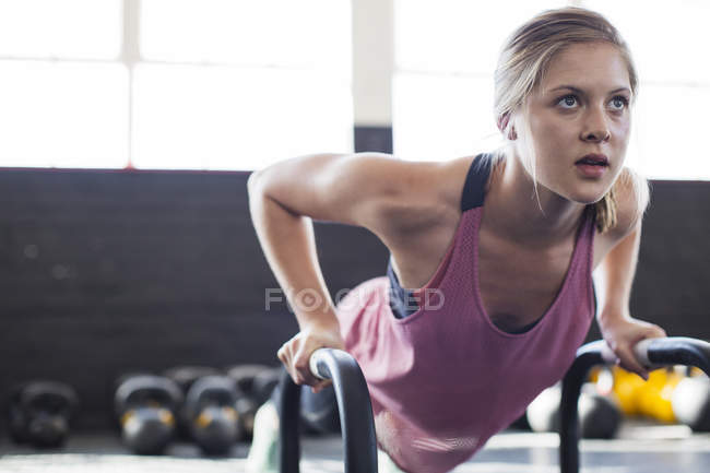 Portrait determined, focused young woman doing push-ups with equipment in gym — Stock Photo