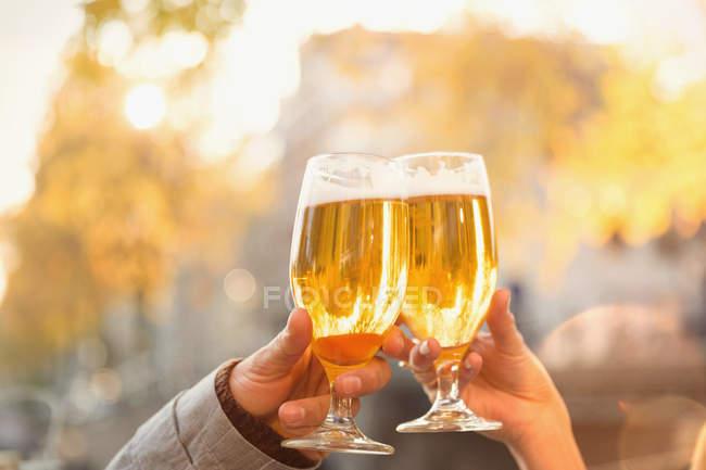 Close up casal brindar copos de cerveja no café de outono — Fotografia de Stock