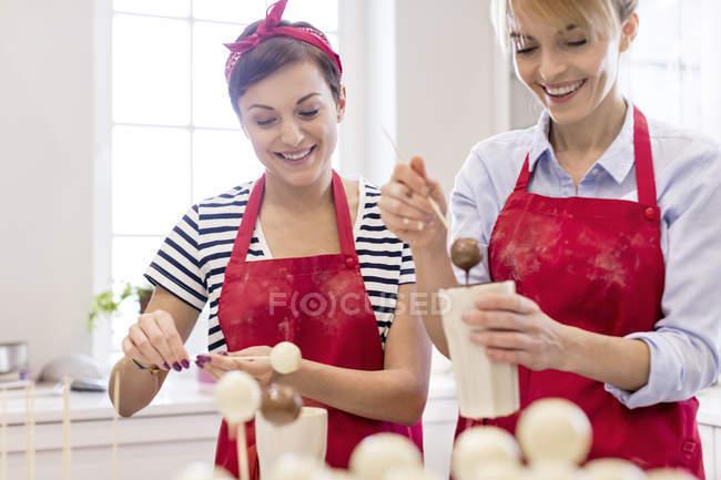 Traiteuses souriantes faisant éclater le gâteau dans la cuisine — Photo de stock