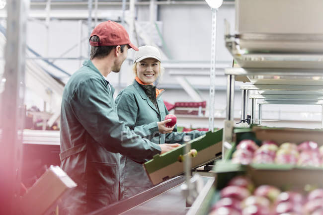 Workers talking and inspecting apples in food processing plant — Stock Photo