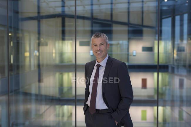 Портрет посміхатися, впевнено бізнесмен сучасні офісні атріум — стокове фото