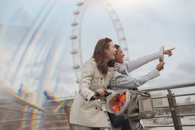 Female tourists with bicycle using digital tablet camera near Millennium Wheel, London, UK — Stock Photo