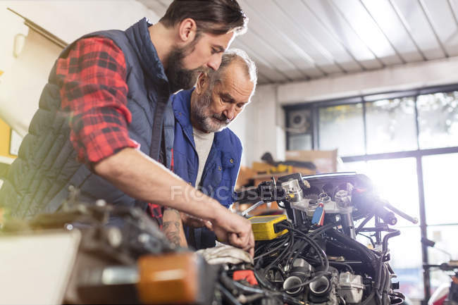 Motorcycle mechanics repairing motorcycle in workshop — Stock Photo