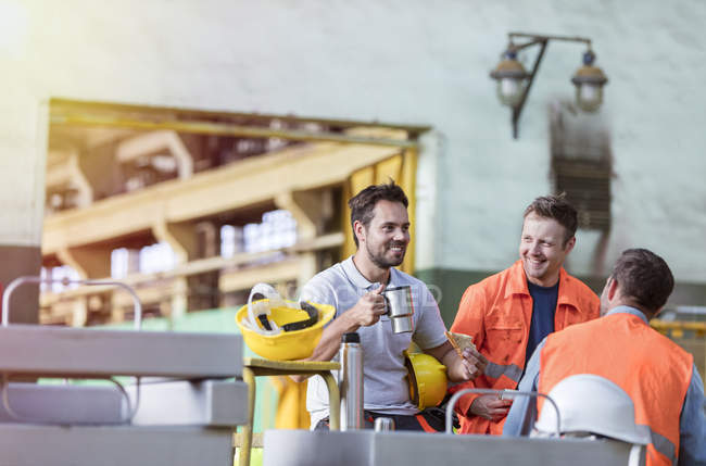 Smiling steel workers enjoying coffee break ins factory — Stock Photo