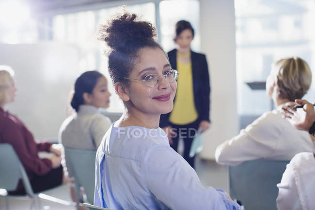 Portrait smiling, confident businesswoman turning, looking back in conference audience — Stock Photo