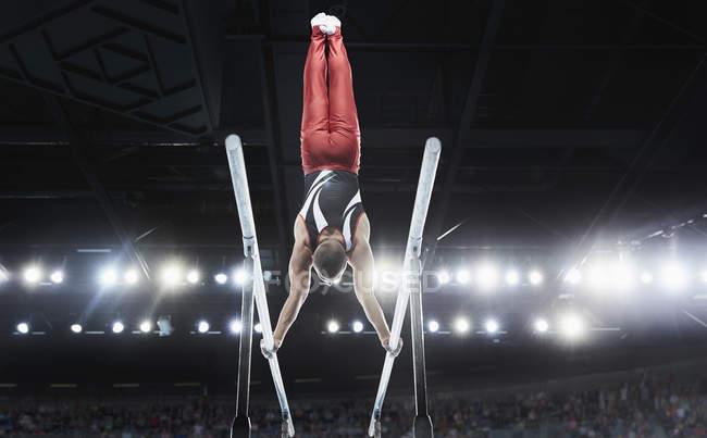 Мужчина гимнаст, выступающий вверх ногами на параллельных брусьях на арене — стоковое фото