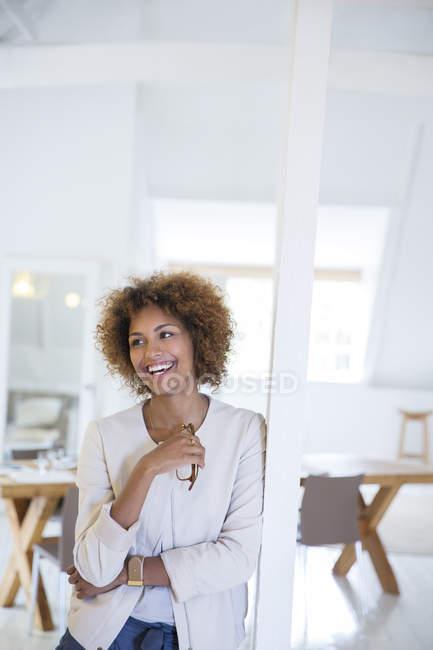 Retrato de mulher apoiando-se na coluna no escritório e sorrindo — Fotografia de Stock
