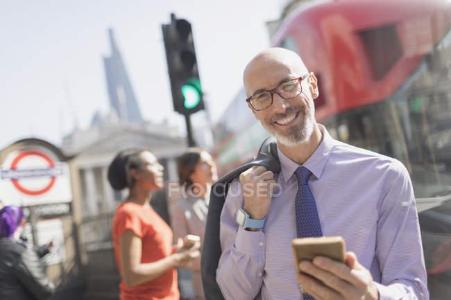 Ritratto uomo d'affari sorridente con cellulare sulla strada urbana soleggiata, Londra, Regno Unito — Foto stock