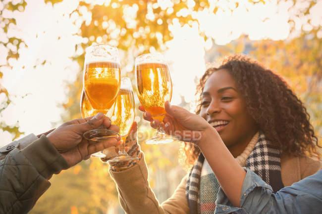 Amigos brindar copos de cerveja ao ar livre — Fotografia de Stock