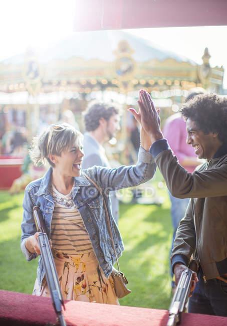 Jeune couple donnant haute cinq dans le parc d'attractions — Photo de stock
