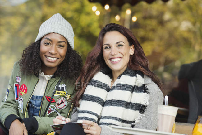Portrait smiling young women friends writing postcard at sidewalk cafe — Stock Photo