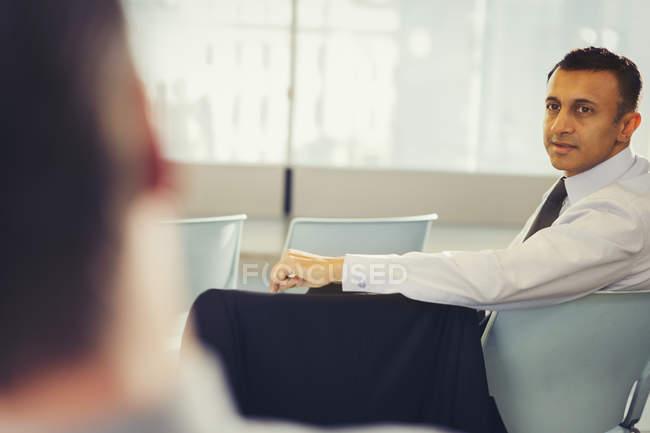 Homme d'affaires tournant, avec le recul et l'écoute dans l'auditoire de la Conférence — Photo de stock