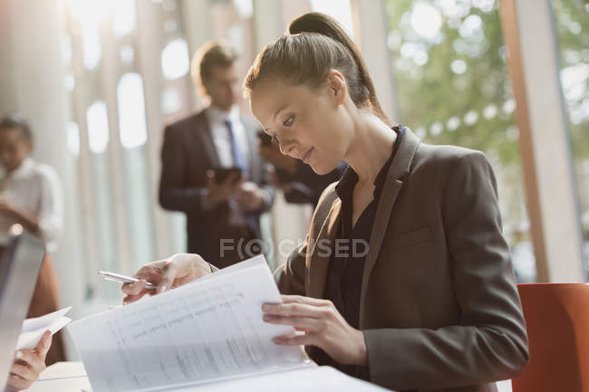 Businesswoman reading reviewing paperwork at modern office — Stock Photo
