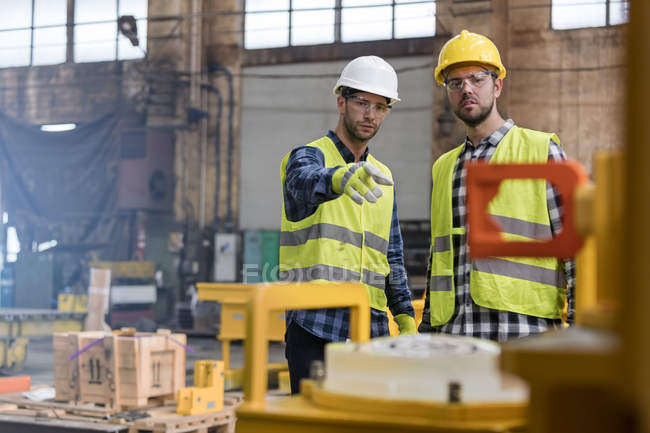 Steel workers talking and pointing in factory — Stock Photo
