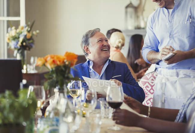 Sonriente hombre con pedido de camarero en mesa de restaurante de menú - foto de stock