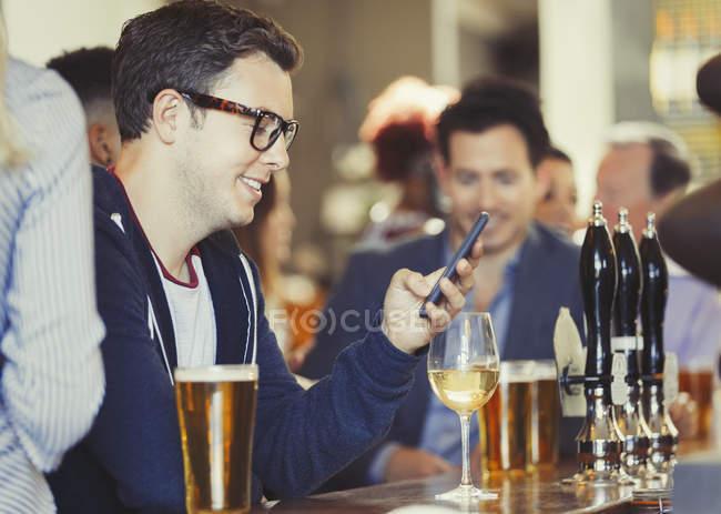 Uomo sorridente che messaggia con il cellulare bevendo vino al bar — Foto stock